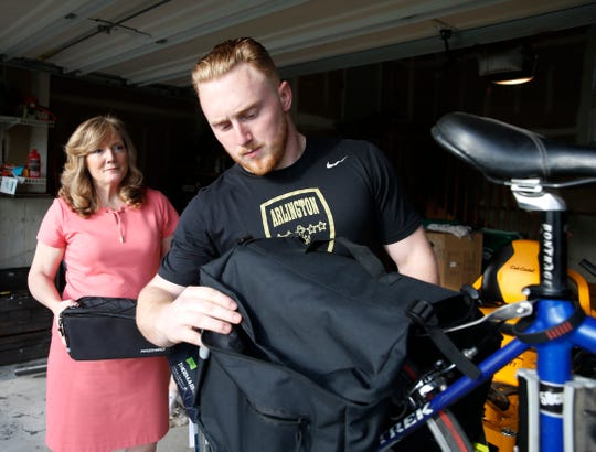 Cintdy Wilson helps her son, Ryan with his cycling equipment at their home in the Town of Poughkeepsie on May 20, 2019. Ryan has decided to ride this bicycle to Miami, Florida to raise money for ALS research.