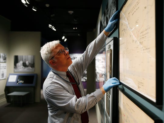 """FDR Presidential Library and Museum supervisory curator Herman Eberhardt inspects one of the situation maps from D-Day on display at the library on May 21, 2019. A new exhibit """"D-Day: FDR and Churchill's 'Mighty Endeavor'"""" opens on May 25th."""