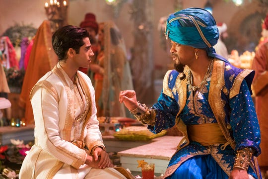 "Mena Massoud as Aladdin, left, and Will Smith as Genie in Disney's live-action adaptation of the 1992 animated classic ""Aladdin."" This image released by Disney shows"