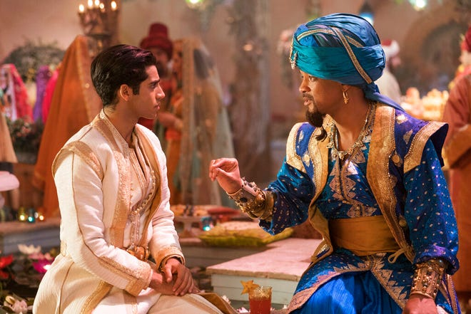 """Mena Massoud as Aladdin, left, and Will Smith as Genie in Disney's live-action adaptation of the 1992 animated classic """"Aladdin."""" This image released by Disney shows"""