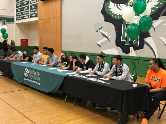 Hug athletes sign for college on Wednesday at the school