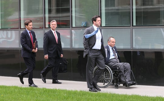 Developer Robert Morgan leaves federal court in Buffalo with his attorneys after being charged with fraud
