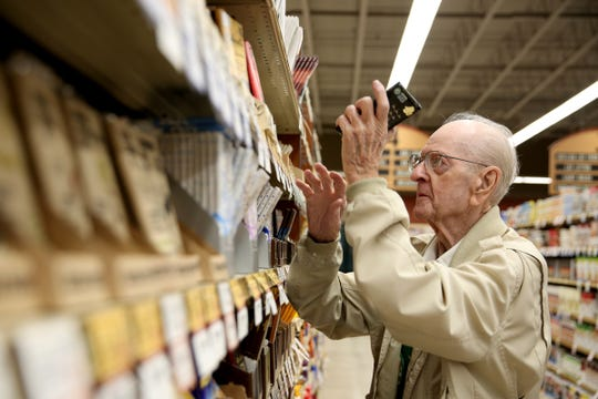 Robert Stone, 92, checks expiration dates on items at the Roth's Fresh Markets at Hayesville in Salem on May 22, 2019. Stone has worked for Roth's for 25 years.