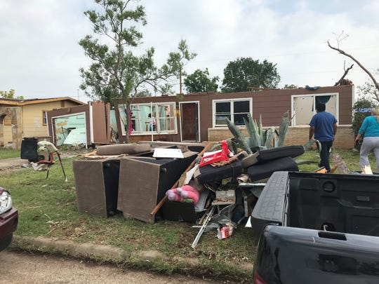 Jose Tellez walks toward his destroyed E. 24th St. home Wednesday, May 22, 2019. His home was hit by a tornado before dawn May 18, 2019.