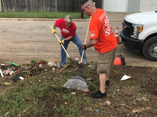 Home Depot supervisor Clay Owen and H-E-B store manager Lynn Shipley rake up debris out of a backyard on E. 24th Street Wednesday, May 22, 2019.