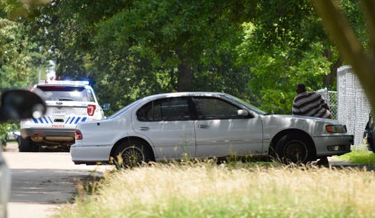 A man watches police attempt to make contact with a male subject inside a home located in the 200 block of East Jordan Street on Wednesday.