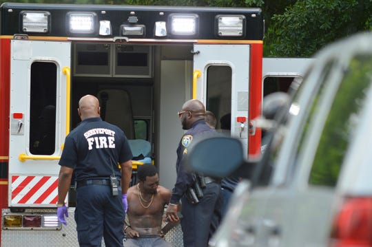 Shreveport police and fire stand with a subject who was taken into custody Wednesday afternoon after law enforcement used chemical agents to get the subject to exit a residence in the 200 block of E Jordan Street.