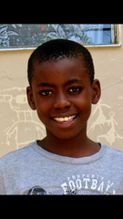 Pierre Lear poses for a photo outside the orphanage he grew up at in Port-au-Prince.
