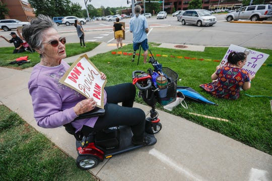 "Donna Howell, left, holds up a sign during the Don't Punish Pain Rally outside of Cox Medical Center South on Wednesday, May 22, 2019. Howell said ""People need to know that this is a bad thing that is happening to people who are in a lot of pain."""