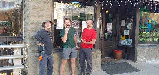 Joseph White, left, and two of his hiking companions outside a restaurant in Hot Springs, North Carolina. White hiked 1,400 miles of the Appalachian Trail this spring and summer.