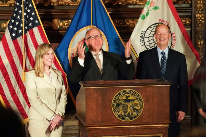 Gov. Tim Walz, center, with Senate Majority Leader Paul Gazelka, right, and House Speaker Melissa Hortman, gestures at a news conference as he was announcing a budget deal in St. Paul, Minn., Sunday, May 19, 2019. Walz and top legislative leaders reached a bipartisan budget deal Sunday in which the governor dropped his proposed gas tax increase but got to keep most of an expiring tax that helps fund health care programs, Republicans got an income tax cut for middle-class Minnesotans and both sides claimed credit for additional spending on education. (Glen Stubbe/Star Tribune via AP)