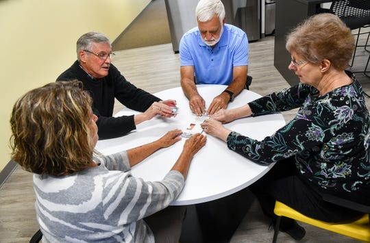 Sue Knauss, Roger Knauss , Jim Schnepf and Connie Nelson prepare cards for the next game after demonstrating a hand of bridge Wednesday, May 22, in St. Cloud.