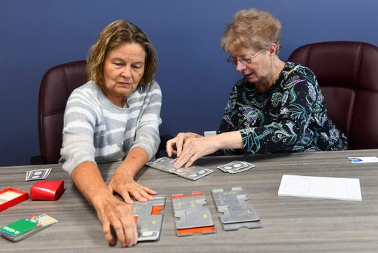Sue Knauss, and Connie Nelson arrange cards into holders used for  bridge Wednesday, May 22, in St. Cloud.
