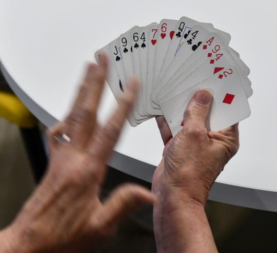 Sue Knauss holds a newly-dealt hand of cards while demonstrating how bridge is played Wednesday, May 22, in St. Cloud.