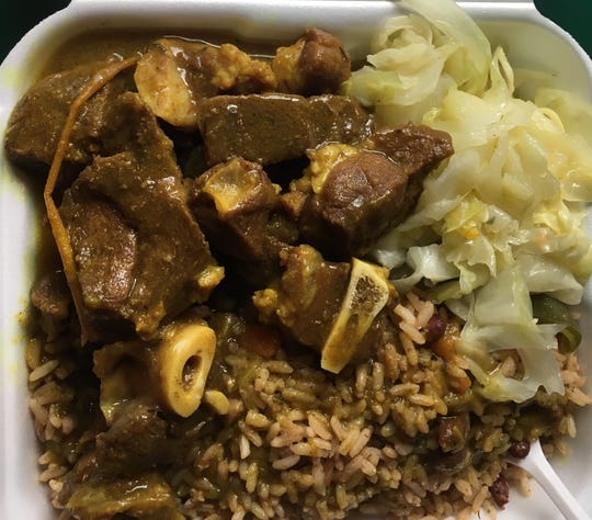 Curried goat with rice and peas and steamed cabbage.