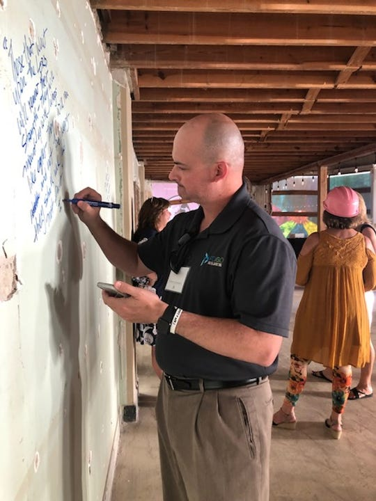 Local business owner Steve Schwartz leaves a message of encouragement on the wall at the new Family Education Center in Vero Beach. Although the messages will be covered up with new drywall, they will always remain a part of the core structure of the 10,000-square-foot building.
