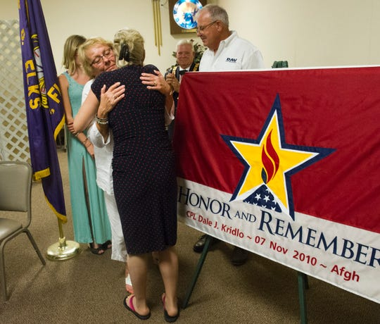 """I need five women to come forward to start a chapter here.  So far, I only have me,"" Michelle Dale (center), hugging friend, Margo Sudnykovych, June 14, 2015 after a Flag Day ceremony in which she was honored with a flag for being an American Gold Star Mother at the Vero Beach Elks #1774 in Vero Beach. The Indian River County Chapter of American Gold Star Mothers finally was installed April 13, 2019. Dale's son, Army Spc. Dale Kridlo was killed in Afghanistan in 2010."
