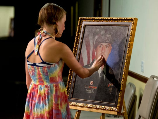 Zoe Kridlo, 13, of Fort Collins, Colorado, was 9 when her father, Army Spc. Dale Kridlo, was killed in Afghanistan on Nov. 7, 2010.  Here, she touches a portrait of him during an event for her grandmother, Michelle Dale (not pictured), of Vero Beach, who was honored as an American Gold Star Mother at the Vero Beack Elks Lodge on Sunday, June 14, 2015.