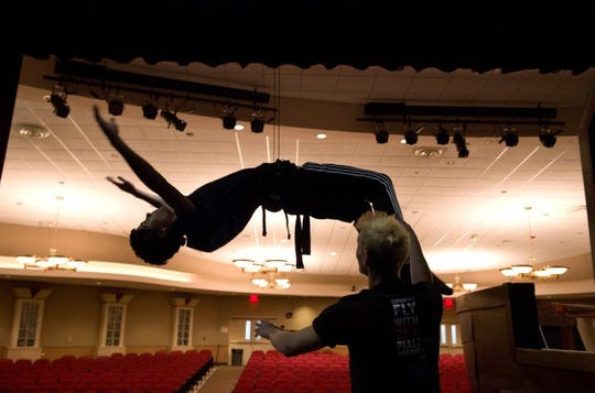 "Journey Velez, 15, who is playing Prince Eric in Port St. Lucie High School's production of ""The Little Mermaid,"" is assisted by flying director Sean Roschman (right) while rehearsing a scene Jan. 21, 2016, in the school's auditorium in Port St. Lucie. Roschman, who works for ZFX Flying Effects, traveled to the school to work with director Patrick Madden to coordinate scenes where the actors fly and simulate movement underwater."
