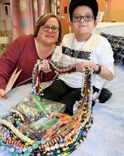 Lead Child Life Specialist Meghan with Mark, a patient, creating Beads of Courage.