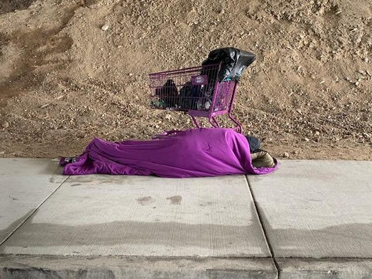 A homeless person sleeps under a Highway 101 overpass in Thousand Oaks on a winter night.