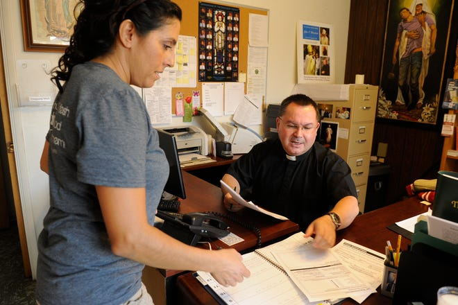In this 2015 photo, youth Director Connie Amezola asks Rev. Raul Diaz to sign some paperwork at the parish office for St. Catherine of Siena Catholic Church in Dinuba.