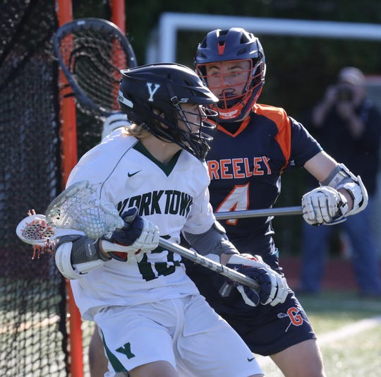 Greeley's Ryan Pohly (4) guards Yorktown's Tim O'Callaghan (15) during boys lacrosse Section 1 Class B semifinal game at Yorktown High School May 21, 2019. Yorktown defeats Greeley 15-6.
