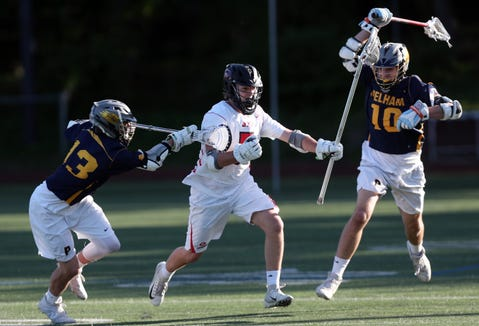Rye's Pat Langer (5) tries to get away from   Pelham's Andrew Clausen (13) and Eddie Dunhill (10) during boys lacrosse playoff action at Rye High School May 21, 2019. Rye won the game 16-3.