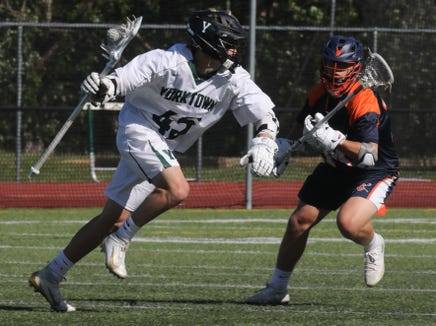 Yorktown's Blake Borges (45) pushes the ball past Greeley's Alex Cottler (14) during boys lacrosse Section 1 Class B semifinal game at Yorktown High School May 21, 2019. Yorktown defeats Greeley 15-6.