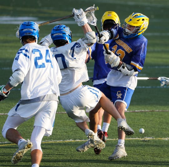 Middletown's Louis Savino loses his footing in a clash with Caesar Rodney's James Cava in the first half of the Riders' 19-6 win in the opening round of the DIAA Boys Lacrosse Tournament on Tuesday night at Cavaliers Stadium.