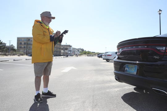 Parking Enforcement Officer for the City of Lewes Clarence Bauman checks the parking status on a car Tuesday, May 21, 2019 at Lewes Beach.