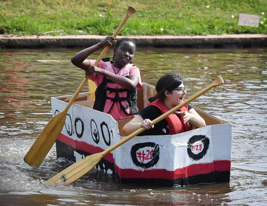 Helen Erua, left, and Alaniss Garcia had difficulty navigating as they cross a section of Sikes Lake in a cardboard boat during the Barwise Boat Float Wednesday morning.
