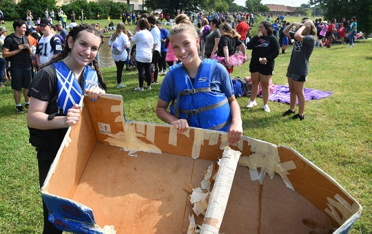 Emma Underhill, left, and Nadia Alden hold what is left of their boat after it sank while crossing a section of Sikes Lake Wednesday during the Barwise Cardboard Boat Float. Students build their boats in Science  class using only cardboard, masking tape, caulk and paint while learning about floatation, bouancy and Newton's Laws of Motion.