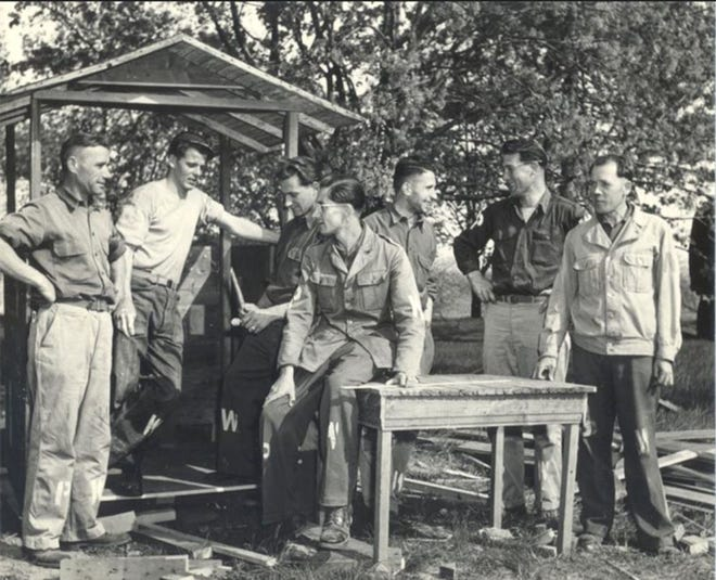 German POW's talking around a table in Door County during World War II. POW's helped harvest cherries and worked in canneries because of a shortage of workers.