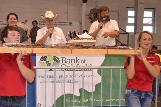 Donning his signature white cowboy hat, Pat O'Brien auctions off the famous 5-foot summer sausage from Brandon Meats and Sausage, held by Alex Costello and Pat's granddaughter, Becca O'Brien.
