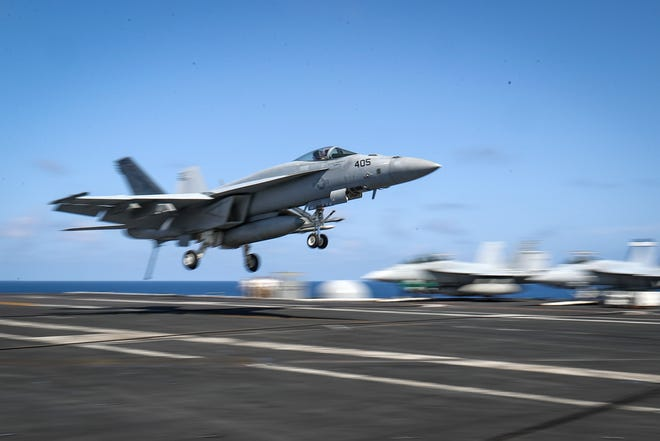 This handout picture released by the US Navy on May 20, 2019 shows a F/A-18E Super Hornet from the Fist of the Fleet of Strike Fighter Squadron (VFA) 25 landing on the flight deck of the Nimitz-class aircraft carrier USS Abraham Lincoln (CVN 72) at the Persian Gulf.