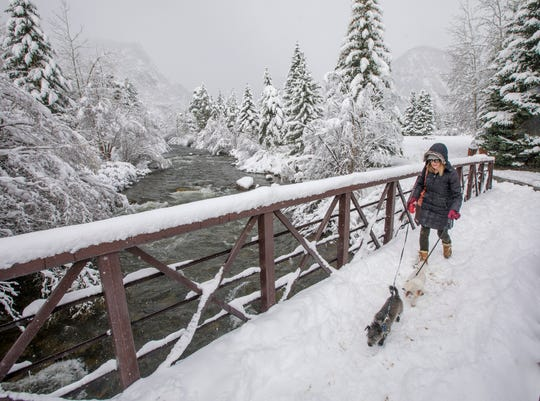 Frisco resident Dianne Stuhr walks with her dogs, Winston and Patty, May 21, 2019, along Tenmile Creek in Frisco, Colo. Nearby Breckenridge Ski Resort reported 9 inches of snow overnight.