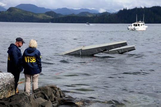 In this May 15, 2019 file photo provided by the National Transportation Safety Board, NTSB investigator Clint Crookshanks, left, and member Jennifer Homendy stand near the site of some of the wreckage of the DHC-2 Beaver that was involved in a midair collision near Ketchikan, Alaska, a couple of days earlier.