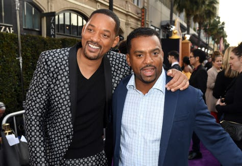 "Will Smith and Alfonso Ribeiro smile for the cameras on their way into the ""Aladdin"" premiere. Sure, Smith stars in the movie. But Ribeiro's signature dance also makes an appearance."