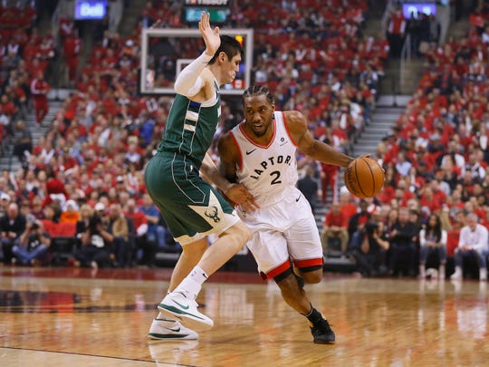 Toronto Raptors forward Kawhi Leonard dribbles the ball around Milwaukee Bucks forward Ersan Ilyasova in Game 4.