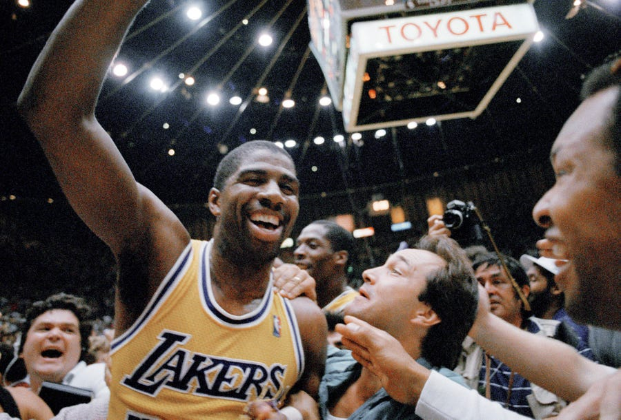 Los Angeles Lakers' Magic Johnson celebrates with fans as he leaves the court after defeating the Boston Celtics.