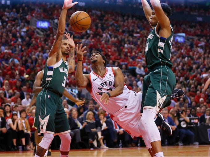 May 21: Toronto Raptors guard Kyle Lowry shoots the ball as Milwaukee Bucks guard George Hill and forward Giannis Antetokounmpo defend during the first half of Game 4 of the Eastern Conference finals.