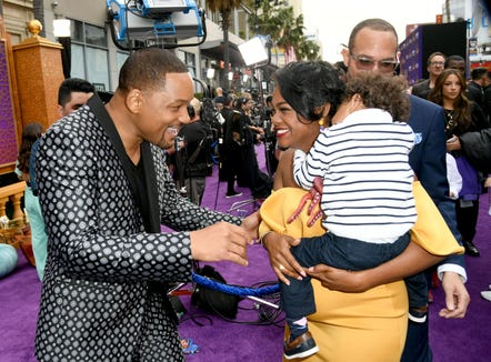 "Tatyana Ali greets with Smith with her son Edward and husband Vaughn Raspberry in tow at the ""Aladdin"" premiere."