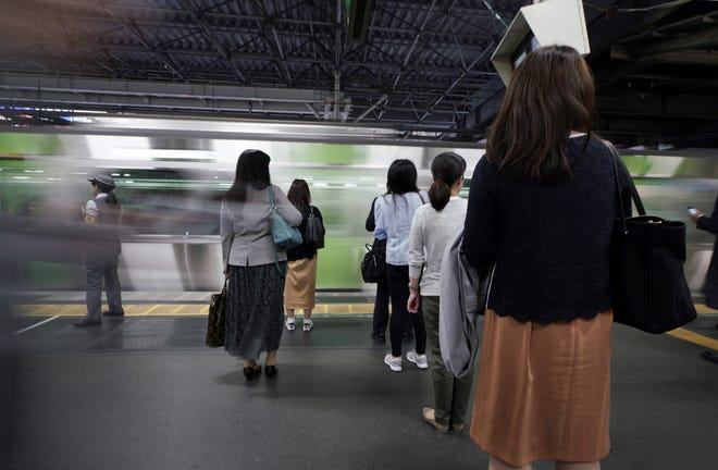 Commuters wait to get on a train at a station in Tokyo. A police-developed smartphone app with anti-sex crime alarms has won massive subscriptions as Japanese women try to arm themselves against gropers on packed rush-hour trains.