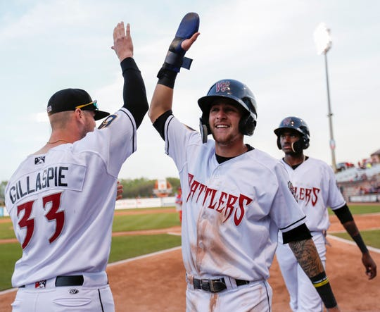 Wisconsin Timber Rattlers' Brice Turang (2) high-fives pitcher Logan Gillaspie (33) during a game against the Peoria Chiefs on May 22 at Neuroscience Group Field at Fox Cities Stadium.