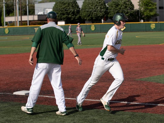 Red Bank Catholic's Shane Panzini gets a hand shake from Caseys' coach Buddy Hausmann as he rounds third after he hit a home run in the bottom of the fifth