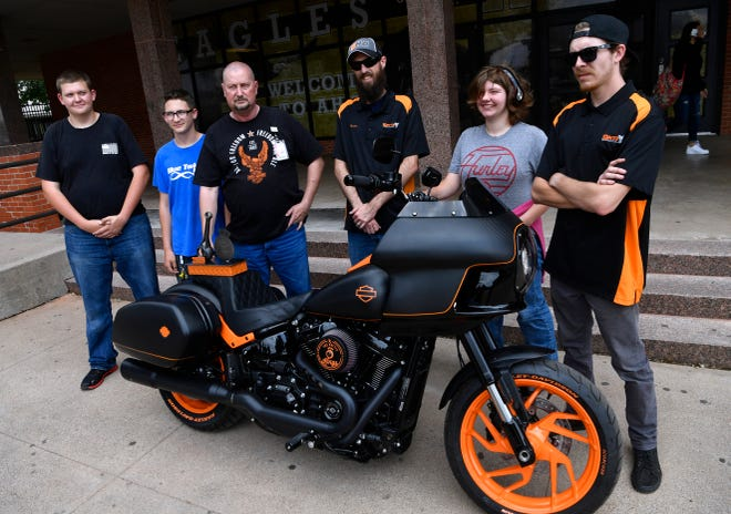 "Winner's of the People's Choice Award for the Harley-Davidson ""Battle of the Kings"" motorcycle-building contest stand before the bike they built Thursday at Abilene High School."