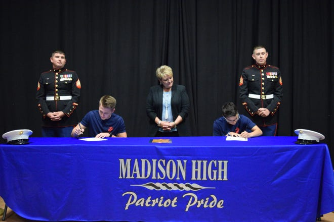 Madison High School seniors Zeke Fender and Taylor Martin committed to four years of service with the U.S. Marine Corps at a ceremony May 16 as the school's principal Rhonda Cuthbertson and recruiters look on.