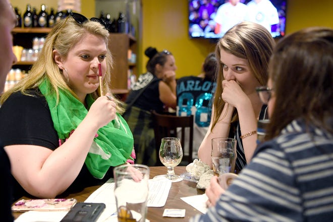 "Members of the team ""The Faux Poes"" Kayla Seay, left, and Sara Kaglic think over the answer to a question as they play Gilmore Girls trivia at The Casual Pint on May 21, 2019."