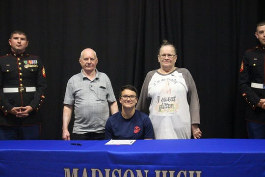 Madison High School senior Taylor Martin sits with her parents Terry Martin and Patricia Lovelace after signing papers to enlist in the Marines.